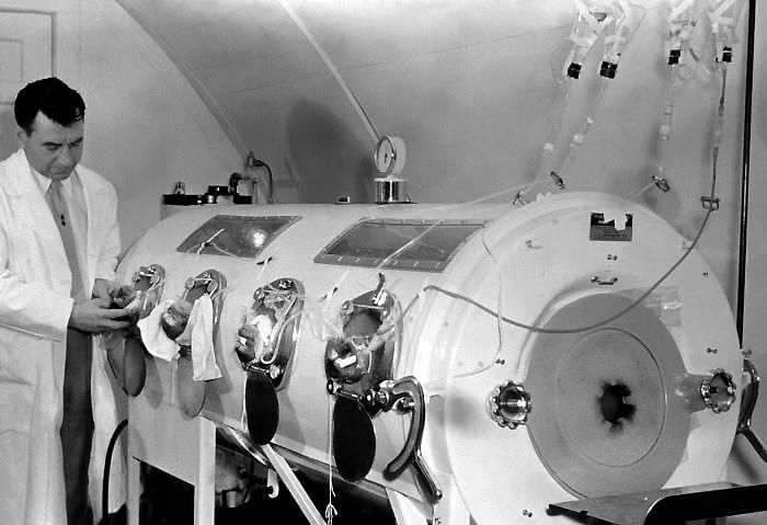 A technician calibrating an iron lung.