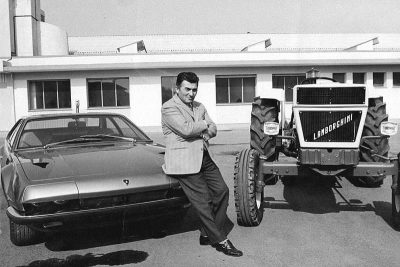 Ferruccio Lamborghini standing between a Lamborghini car and a tractor.