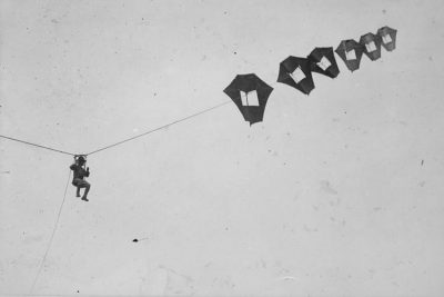 A lieutenant being lifted up in the sky by giant Perkins man-carrying kite.