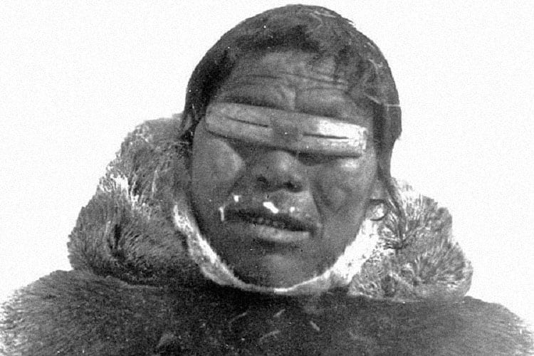 An Inuit wearing native snow goggles.