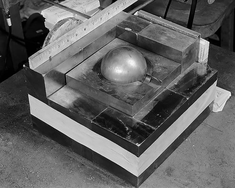 Reflective blocks being placed around a sphere of plutonium.