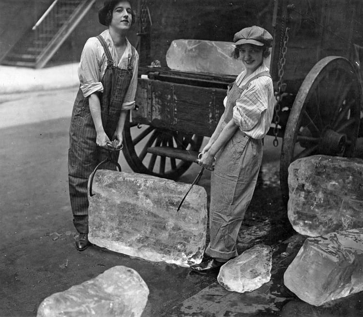 Young women delivering blocks of ice from an ice wagon.