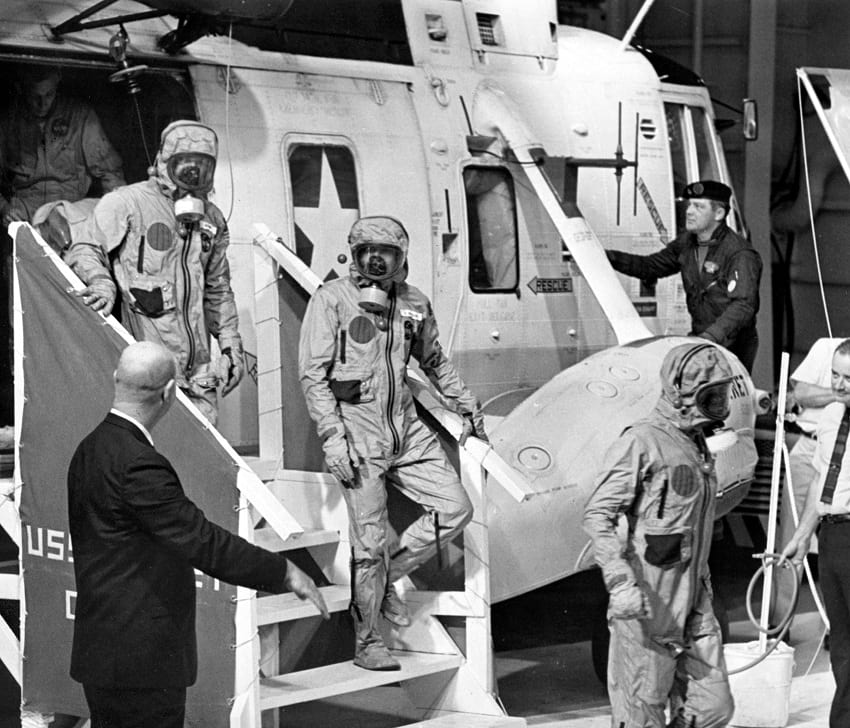 Apollo 11 astronauts exiting the recovery pick up helicopter.