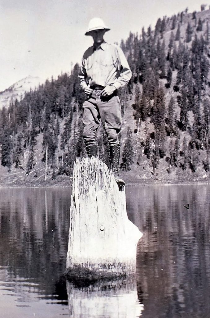 A man standing on the Old Man of the Lake.